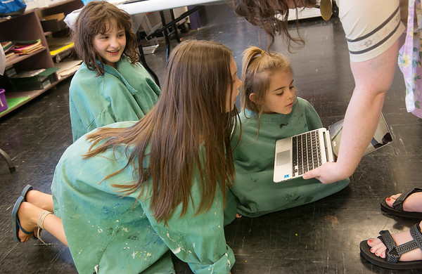 Globe/Roger Nomer<br /> (from left) Aubrey Hasty, 10, Rayna Wiebelhaus, 8, and Stella Beezley, 6, check out photos of action painting before attempting the technique on their own on Tuesday at Spiva Center for the Arts.
