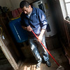 Globe/Roger Nomer<br /> Carlos Diaz mops mud at his home in Kendricktown on Tuesday.