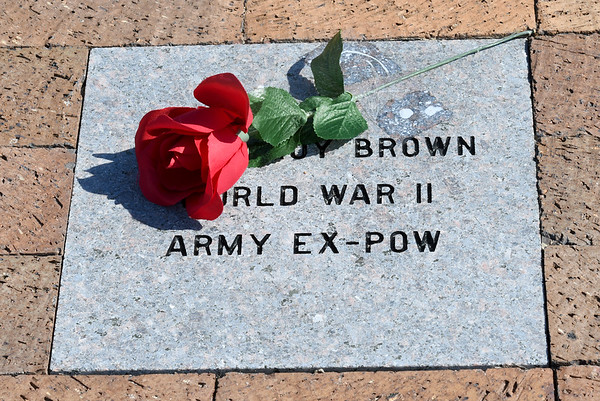 A solitray rose, laid upon a memorial paver at the Pittsburg State University Veterans Memorial, commemorates the service and sacrifice of Leroy Brown, an ex-POW during World War II.<br /> Globe | Laurie Sisk commemorates the service of Lerpy Brown.