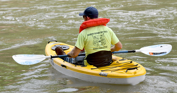 Danny Patrum, of Joplin, searches for extended family member, 12-year-old Brooke Robinson, who was swept away in Shoal Creek on Monday. <br /> Globe  Laurie Sisk