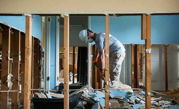 Globe/Roger Nomer<br /> Todd Crane, Tucson, Ariz., clears drywall on Wednesday in a house in Neosho as he volunteers with Team Rubicon.