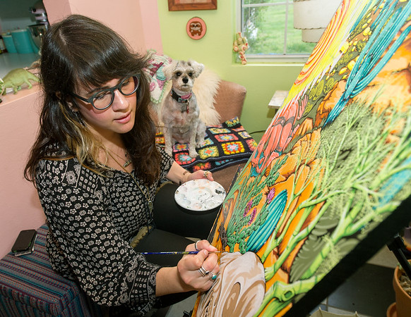 """Carthage artist Martha Goldman works from her at home studio as her dog, """"Bowie"""" looks on last March. <br /> Globe 