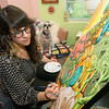 "Carthage artist Martha Goldman works from her at home studio as her dog, ""Bowie"" looks on last March. <br /> Globe 