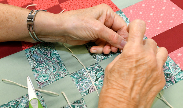 Judy Korn ties off part of a quilt on Thursday at the First United Methodict Church in Carthage.<br /> Globe | Laurie Sisk