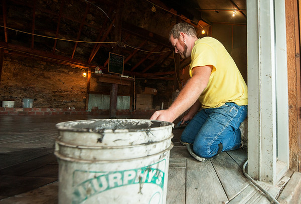 Jacob Gunther helps install new flooring during remodeling of The Undercliff, a popular restaurant that will be reopening in Tipton Ford.<br /> Globe | Laurie Sisk