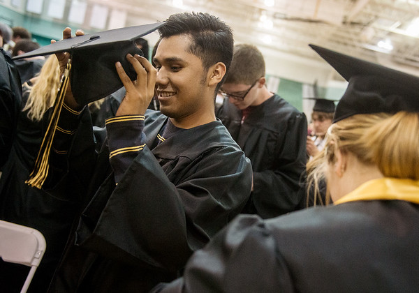 Globe/Roger Nomer<br /> Bryan Bernal, Neosho High senior, tries on his cap and gown on Wednesday during graduation practice at the Leggett and Platt Athletic Center.