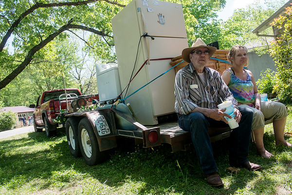 Globe/Roger Nomer<br /> Jerry Hoover waits with his granddaughter Erica Bullard while volunteers remove carpeting from his house in Neosho on Monday.