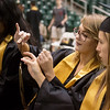 Globe/Roger Nomer<br /> Kaitlyn Williams, left, and Kenzie Williams, Neosho seniors, loop their tassels on Wednesday during graduation practice at the Leggett and Platt Athletic Center.