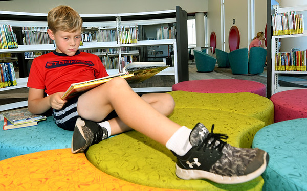 Eight-year-old Bennett Robertson, of Carl Junction, relaxes with a book about World War II inside the new Joplin Public Library on Tuesday. Tuesday marked the opening day of the new library.<br /> Globe | Laurie Sisk