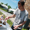 Globe/Roger Nomer<br /> Volunteer Matthew Brown serves food provided by Operation BBQ relief on Monday at the Lampo building in Neosho.