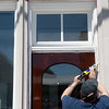 Globe/Roger Nomer<br /> Randy Brownell works on the exterior of the 200 Block Commons building on Friday.