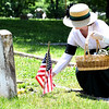 Historical reeanctor Emily Ellis, dressed in 1918-style clothing, lays a single yellow rose on the grave of World War I soldier Harold Otto Wheeler during a walkthrough Memorial of WWI soldiers on Memorial Day at the Carterville Cemetery.<br /> Globe | Laurie Sisk
