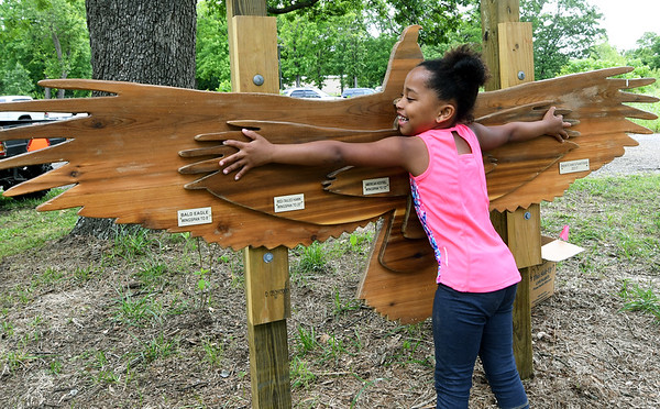 Six-year-old Aliyah Presley compares her wingspan to that of a bald eagle at the new children's park at Wildcat Glades on Wednesday.<br /> Globe | Laurie Sisk