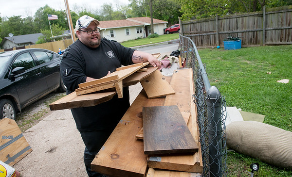 Globe/Roger Nomer<br /> Matt Quick takes a damaged bed frame out to the street for pick up on Monday in Neosho.