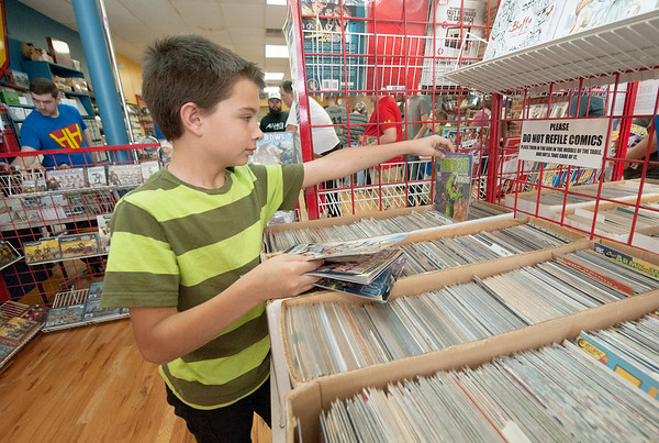 Twelve-year-old Gage Allen checks out the selection of comics during Free Comic Book Day on Saturday at Hurley's Heroes Comics.<br /> Globe | Laurie Sisk