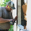 Globe/Roger Nomer<br /> Jason Letts, with Robert Peters Investments, helps repair a window on a house in Neosho on Monday.