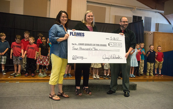 Globe/Roger Nomer <br /> Martin Luther School Principal Jeremy Schamber presents Camp Quality of the Ozark representatives Denise Dieckhoff, volunteer coordinator, left, and Kristin Patterson, co-executive director, with a check for $4,000 on Tuesday at the school. Students raised the money for the camp through chapel offerings and tithes from fundraisers.