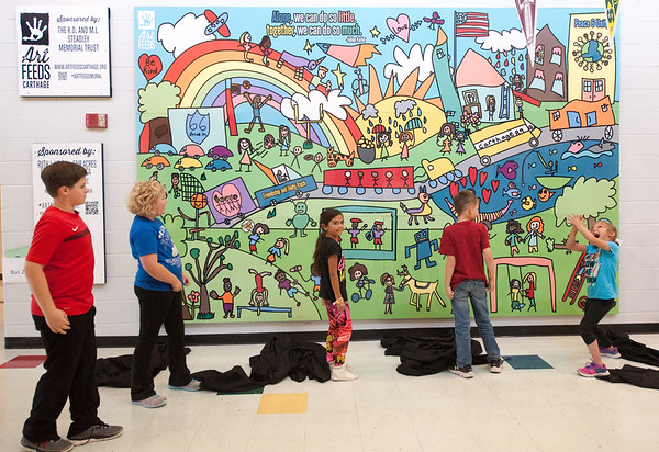 From the left: Steadley Elementary fourth grader Lance Pyron, third grader Libbie Worrall, second grader Audrie Brooks, first grader Tucker Reed and kindergartner Allie Brown unveil a new mural for their school on Friday afternoon in Carthage. The mural was sponsored by Art Feeds Carthage, The K.D. and M.I. Steadley Memorial Trust, the Ruth I. Koplin Foundation, Fair Aces YMCA, Schmidt Associates PC and the Parish Council of Catholic Women.<br /> Globe | LAurie Sisk