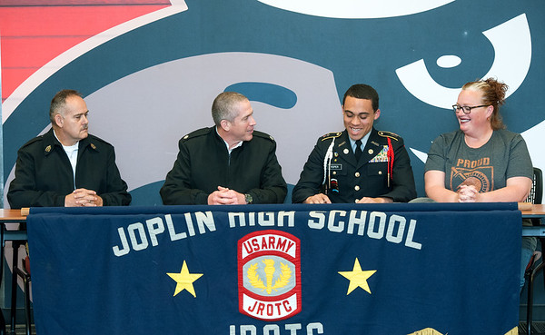 Joplin High School Cadet Lt. Col. Othellis Roper III, second from the right, smiles as he signs his acceptance letter into the West Point Academy on Wednesday at JHS.  Also pictured, from the left JROTC 1st Sgt. Richard Banhs, Lt, Col. Joshua Reitz and Roper's mother, Stephanie Roper.  Reiyz said, to the best of his knowledge, Roper is the firsy JHS cadet accepted into a military academy in about 12 years.<br /> Globe | Laurie Sisk