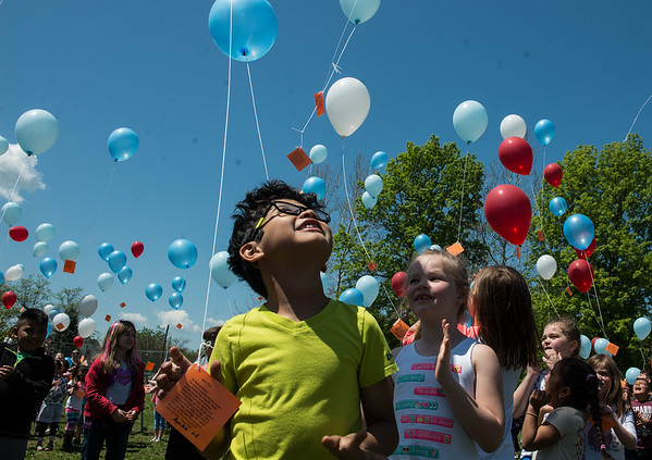 Luis Ramirez, first grader at Mark Twain Elementary, lets go of his balloon during Monday's balloon launch at the school.<br /> Globe | Roger Nomer