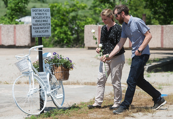 Anna and Simon Buchel places white roses at a ghost bike serving as a memorial to their father Heinz-Gerd and his friend Harry Jung in Galena on Friday.<br /> Globe | Roger Nomer