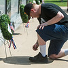 Henry Silvey kneels in prayer in front of a wreath honoring Army soldiers at the Veterans Memorial in Mount Hope Cemetery on Monday. Silvey is an Afghanistan veteran who served in the Army.<br /> Globe | Roger Nomer