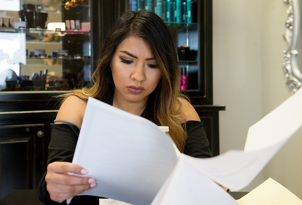 Glendry Lopez looks over paper work on Monday after being sued by her former salon.<br /> Globe | Roger Nomer