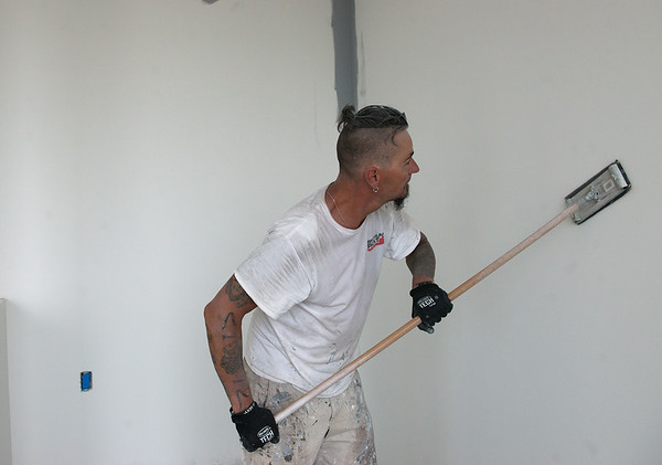 Tommy Foster, with Finishing Touch, sands a wall at the Block 22 apartments on Tuesday in Pittsburg. <br /> Globe | Roger Nomer