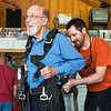 Jim Oglesby shows his excitement for his jump as he is strapped into his safety gear by Brad Barnett on May 19 at the Ozark Skydive Center.<br /> Globe | Roger Nomer