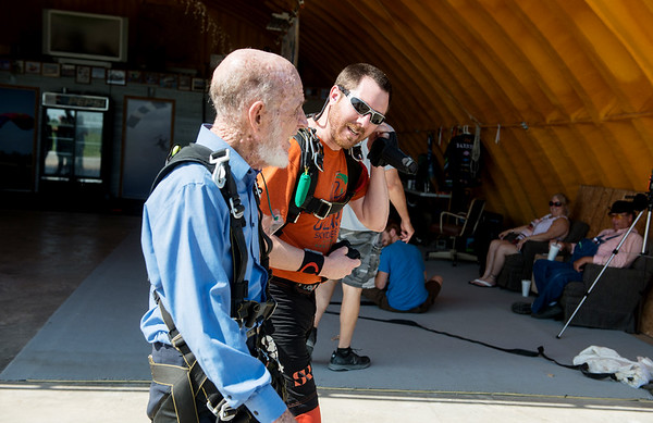 Jim Oglesby talks with his tandem jump partner Brad Barnett on the way to the plane on May 19.<br /> Globe | Roger Nomer