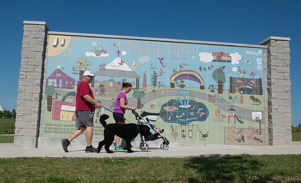 "Matt and Stephanie Grooms, with their dog Kodi, walk by the new Art Feeds mural in Mercy Park on Monday. ""Together We Create"" was produced by area children in conjuction with Art Feeds, with funding provided by Mercy Hospital Joplin. The mural was unveiled this past Saturday.<br /> Globe 