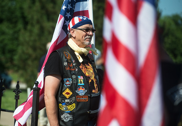 Robert Bachert holds a flag during a Memorial Day ceremony at Mount Hope Cemetery on Monday.<br /> Globe   Roger Nomer