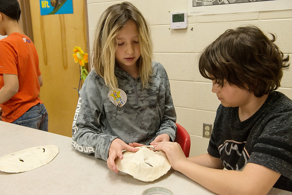 Addysen Ball and Konnor Aragon, Granby Elementary fourth graders, work on a paper mask on Wednesday at the school.<br /> Globe | Roger Nomer