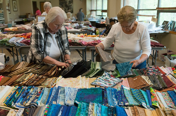 Delphia Dart, left, and Barbara Pipkin help sort fabrics during the Fabric and Needlework Sale to benefit the Wildcat Glades Friends Group on Friday at the Wildcat Glades Conservation & Audubon Center. The sale continues today from 9 a.m. to 5 p.m., with items marked to half price at noon.<br /> Globe | Roger Nomer
