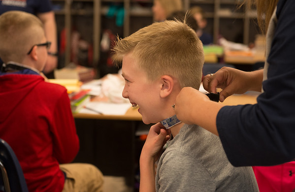 Cooper Williams, a fifth grader at St. Mary's Elementary, reacts to wearing a velcro collar, which is meant to simulate having autism during a presentation on Monday.<br /> Globe | Roger Nomer