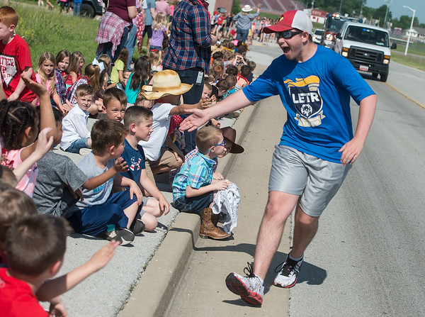 Cail Tingle, 16, gets high fives from kindergarten students at Madge T. James Elementary on Tuesday during the 2018 Law Enforcement Torch Run.<br /> Globe | Roger Nomer