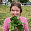 Tessa Miller, third grade, shows spinach she picked in the West Central Elementary garden on Monday.<br /> Globe | Roger Nomer