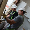 Zack Wood, left, and Larry Handshy, with Wilson Builders, work on a window at the Block 22 apartments on Tuesday in Pittsburg. <br /> Globe | Roger Nomer
