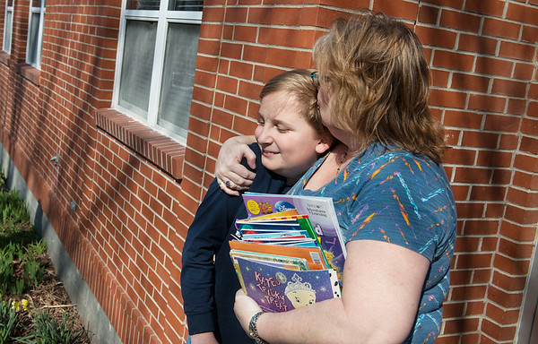 Dawn Lewis gives her grandson Kevin Kelley, McKinley Elementary fourth grader, a kiss as they watch children's books unloaded at Lafayette House on Thursday.<br /> Globe | Roger Nomer