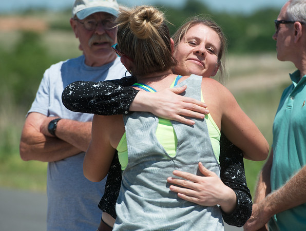 Anna Buchel, right, gets a hug from Jennifer Niewald, Joplin, after visiting the ghost bike dedicated to her father Heinz-Gerd and Harry Jung in Galena on Friday.<br /> Globe | Roger Nomer