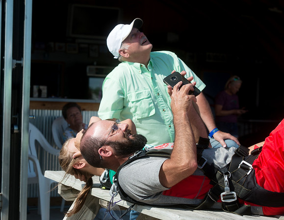 Neil Oglesby, grandson of Jim, left, and Lance Nichols, family friend, watch as Jim Oglesby jumps out of a plane on May 19 at the Ozark Skydive Center.<br /> Globe   Roger Nomer