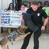 Ax and Brett Davis, Joplin Police K-9 officer, give a demonstration during Tuesday's Safety Fair at Missouri American Water. In addition to demonstrations, the fair showcased safety equipment for employees and community partners.<br /> Globe | Roger Nomer