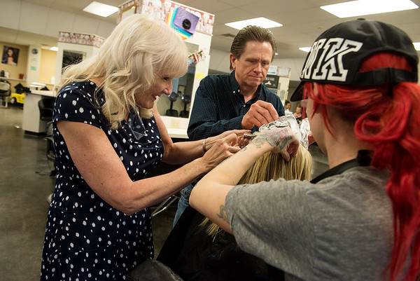 Sharon and Dennis Clements, owners of New Dimensions School of Hair Design, work with a student on Friday at the school.<br /> Globe | Roger Nomer