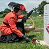 Emily Ellis lays flowers on the grave of WWI veteran Elmer Charboneau on Monday at Carterville Cemetery.<br /> Globe | Roger Nomer