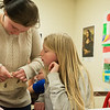 Teanna Brown, a Granby eighth grader, helps Johny Howard, fourth grade, with her paper mask on Wednesday at Granby Elementary.<br /> Globe | Roger Nomer