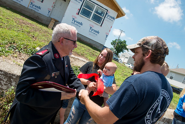 Salvation Army Major Doug Stearns congratulates Jaclyn, Seth and Atlas, 8 months, Hurtt on their new home on Monday in Joplin.