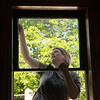 Lori Haun works on a window at the Schifferdecker House on Friday.<br /> Globe | Roger Nomer