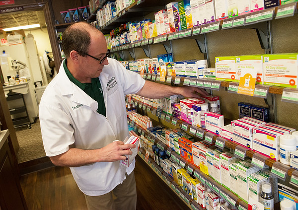 Tim Mitchell, pharmacist and owner, works at Mitchell's Downtown Drug Store on Friday in Neosho.<br /> Globe | Roger Nomer
