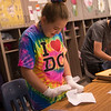 Bethany Lone, a fifth grader at St. Mary's Elementary, tries to make a paper airplane while wearing socks on her hands during a presentation on autism on Thursday.<br /> Globe | Roger Nomer