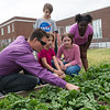Michael Wischmeyer works with (from left) Juno Fitzhugh, Owen Siebenthal, Tessa Miller and Harmony Crayton, third graders, on a garden at West Central Elementary on Monday.<br /> Globe | Roger Nomer